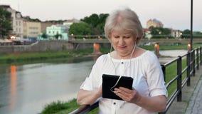 Bejaarde die tabletcomputer met oortelefoons met behulp van dichtbij het traliewerk op waterkant in avondtijd, oude stad, rivier  stock video