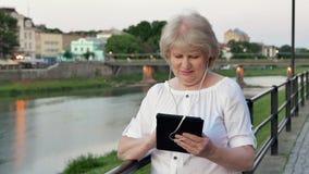 Bejaarde die tabletcomputer met oortelefoons met behulp van dichtbij het traliewerk op waterkant in avondtijd, oude stad, rivier  stock videobeelden