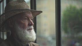 Bejaarde die uit venster kijkt stock footage