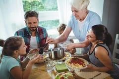 Bejaarde dienende maaltijd aan haar familie Royalty-vrije Stock Afbeeldingen