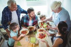 Bejaarde dienende maaltijd aan haar familie Stock Afbeeldingen
