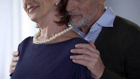 Bejaarde echtgenoot die vrouw in parels op schouder, speciale gelegenheid, geluk koesteren stock afbeeldingen