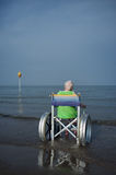 Bejaarde in een rolstoel in het overzees royalty-vrije stock afbeeldingen