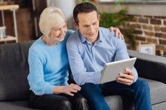 Bejaarde en haar zoon die door foto's op tablet kijken royalty-vrije stock afbeeldingen