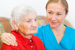 Bejaarde en jonge werker uit de hulpverlening Stock Afbeeldingen
