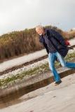 Bejaarde energieke mens die langs een strand lopen Royalty-vrije Stock Afbeeldingen