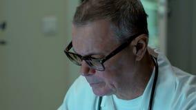 Bejaarde ervaren arts met stethoscoop die aan laptop computer op zijn kantoor werken Hij draagt witte schone laag, stock videobeelden
