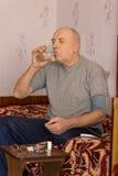 Bejaarde geamputeerdezitting die zijn medicijn nemen Stock Foto's