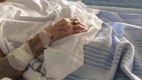 Bejaarde geduldige slaap op een medisch bed in het ziekenhuisafdeling stock video