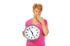 Bejaarde geeuwende vrouw die grote klok houden Stock Fotografie