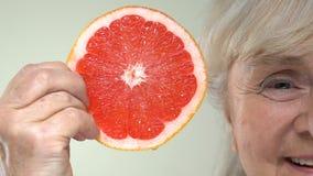 Bejaarde glimlachende vrouw die grapefruitplak tonen, anti-verouderend voedsel, dieetcalorieën stock footage