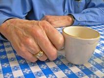 Bejaarde hand met koffiekop royalty-vrije stock foto