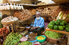 Bejaarde handelaar die van gember, kokosnoten en andere groenten op klanten bij landbouwersmarkt wachten Royalty-vrije Stock Afbeelding