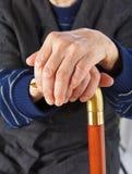 Bejaarde handen die op stok rusten Stock Foto's