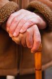 Bejaarde handen die op wandelstok rusten Stock Afbeeldingen