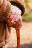 Bejaarde handen die op wandelstok rusten Stock Foto