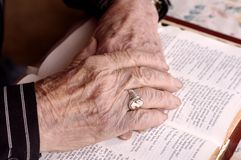 Bejaarde handen op bijbel Stock Foto's