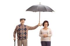 Bejaarde heer die een paraplu over een bejaarde dame houden stock foto's