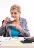 Bejaarde het bedrijfsvrouw drinken thee of koffie bij bureau in bureau, onderbreking op het werk Stock Foto