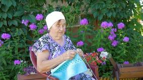 Bejaarde het breien zitting op de straat buiten zijn huis stock video