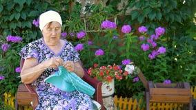 Bejaarde het breien zitting op de straat buiten zijn huis stock footage
