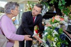 Bejaarde het kopen bloemen bij de begrafenisdienst royalty-vrije stock foto's