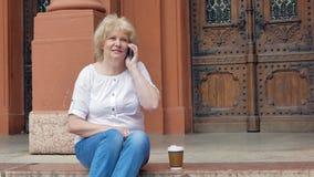 Bejaarde het spreken op smartphone en drinkt koffie De uitstekende bouw op de achtergrond stock video