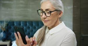 Bejaarde het texting op smartphone stock video