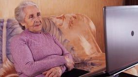 Bejaarde het typen op laptop terwijl het zitten op de laag Metaallaptop stock footage