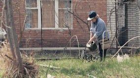 Bejaarde het water geven installaties van het water geven van pot in tuinbinnenplaats stock footage