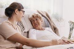 Bejaarde in het ziekenhuisbed met maatschappelijk werker die haar helpen stock afbeelding