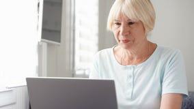 Bejaarde hogere blonde vrouw die aan laptop computer thuis werken Het verre freelance werk aangaande pensionering stock afbeeldingen