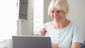 Bejaarde hogere blonde vrouw die aan laptop computer thuis werken Ontvangen goed opgewekt en gelukkig nieuws royalty-vrije stock foto