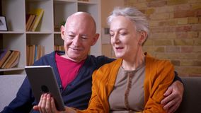 Bejaarde Kaukasische echtgenoten die in tablet letten op en het disussing die positief en blij bij bank in woonkamer zijn stock footage