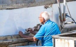 Bejaarde Kaukasische mens die een boot op een zonnige dag schilderen Royalty-vrije Stock Afbeelding