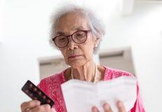 Bejaarde Kaukasische vrouw met geneeskunde en lezingsdrugvoorschrift stock foto's