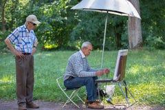 Bejaarde kunstenaar en toeschouwer in het de zomerpark royalty-vrije stock afbeeldingen