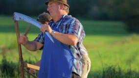 Bejaarde landbouwer tolkes aan de vrouw terwijl de man het gras maait stock videobeelden
