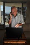 Bejaarde laptop gebruiker op de telefoon voor steun Royalty-vrije Stock Afbeelding