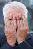Bejaarde manager met ogen op handen royalty-vrije stock afbeelding