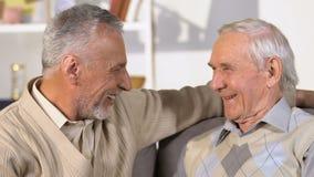 Bejaarde mannelijke en vrienden die, samenkomende broers, vakantiegroet spreken koesteren stock videobeelden