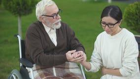 Bejaarde mannelijke troostende die dame met slechte diagnose, bezoek aan verpleeghuis wordt verstoord stock footage