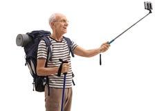 Bejaarde mannelijke wandelaar die een selfie met een stok nemen stock afbeeldingen