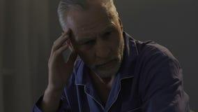 Bejaarde mannelijke zitting op bed in donkere ruimte, die zijn tempels, sterke hoofdpijn wrijven stock videobeelden