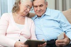 Bejaarde mensen Bejaarde laptop van de paarholding, smartphone en maakt aankopen over Internet in de comfortabele woonkamer van h royalty-vrije stock afbeeldingen