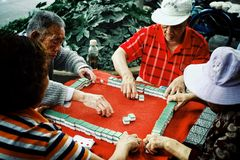 Bejaarde mensen die mahjong en kaarten in een park spelen openlucht royalty-vrije stock afbeelding