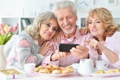Bejaarde mensen die ontbijt hebben en mobiele telefoon met behulp van royalty-vrije stock afbeelding