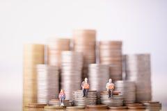 Bejaarde mensen die op muntstukkenstapel zitten Pensionering Planning stock afbeeldingen