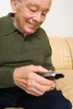 Bejaarde met afstandsbediening Royalty-vrije Stock Afbeeldingen