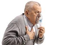 Bejaarde met astma gebruikend een inhaleertoestel en houdend zijn borst stock foto's
